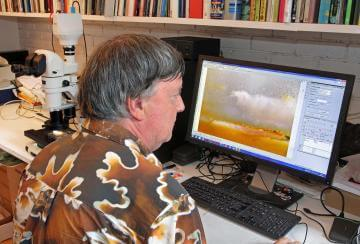 nikon metrology prof robert weston wearing a shirt printed with one of his ammonite fossil photographs examines the agate crystal on the screen of the linked pc large